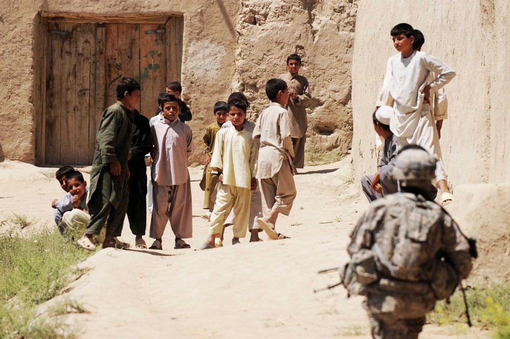 Young and innocent children from Afghanistan looking at a solider approaching them
